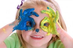 Dziewczynka w żłobku bawi się farbami